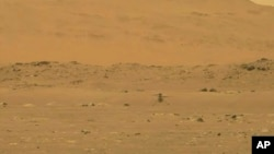 In this image from NASA, NASA's experimental Mars helicopter Ingenuity lands on the surface of Mars Monday, April 19, 2021. (NASA via AP)