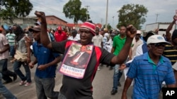 A demonstrator dances as he carries a picture of Haiti's former President Jean-Bertrand Aristide during a march against President Martelly, Sept. 30, 2013.