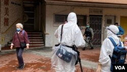 On Feb. 11, 2020, an AP crew in full protective gear is filming in front of the Tsing Yi public housing building in Hong Kong. Two units in the building had confirmed coronavirus cases and other residents were evacuated. (Photo taken by VOA Cantonese stringer Iris Tang)