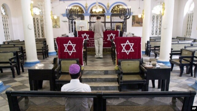 FILE - Moses Samuels sits alone at the synagogue in Rangoon, as his son Sammy Samuels reads from a prayer book, May 2, 2001.