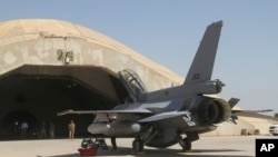 FILE - This July 2015 file photo shows one of four new U.S.- made F-16 fighter jets outside a hardened hangar upon its arrival to Balad air base, north of Baghdad, Iraq.