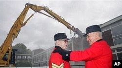 Chelsea pensioners Bill Lunsden, left, is comforted by colleague Paddy Fox as they watch the demolition of the old infirmary at the Royal Hospital Chelsea in west London. The Old Infirmary of the Royal Hospital Chelsea is being demolished to modernize the