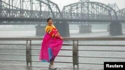 지난 2010년 6월 중국 단둥과 북한 신의주를 잇는 다리를 배경으로 한복을 입은 관광객이 포즈를 취하고 있다.