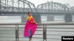 지난 2010년 6월 북-중 접경에서 단둥과 신의주를 잇는 다리를 배경으로 한복을 입은 관광객이 포즈를 취하고 있다. (자료사진)