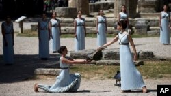 High Priestess Katerina Lehou, (r) lights a pot with a backup flame for the Rio Olympics in front of the ancient temple of Hera, during the dress rehearsal for the lighting of the Rio Olympics flame, in Ancient Olympia, Greece, April 20, 2016.