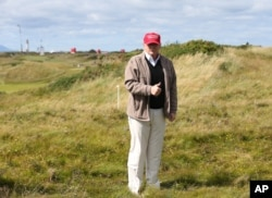 FILE - Donald Trump gestures to the media on the Turnberry golf course in Turnberry, Scotland, July 30, 2015.
