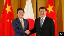 资料照:中国国家主席习近平和大阪与日本首相安倍晋三握手。(2019年6月27日)