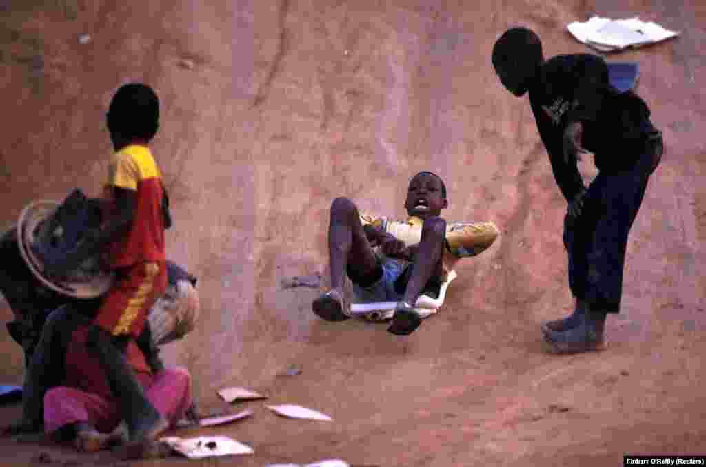 Rapazes brincam deslizando com um pedaço de plástico por uma colina do Lubango