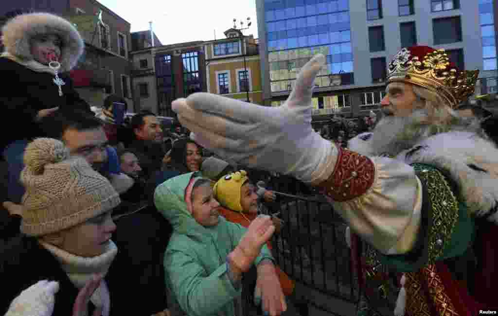 Un hombre disfrazado como uno de los Tres Reyes Magos saluda a los niños que asistieron al desfile de la Epifanía en Gijón, al norte de España, el cinco de enero del 2019.