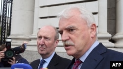 Independent Alliance Ministers, Shane Ross (L) and Finian McGrath speak to the press on arrival at Government buildings for a cabinet meeting in Dublin on Sept. 2, 2016 on whether to appeal an EU order mandating Ireland to collect €13 billion in taxes fro