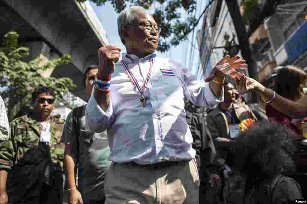 Protest leader Suthep Thaugsuban gestures as he collects money from a supporter during a rally in central Bangkok, Jan. 30, 2014.