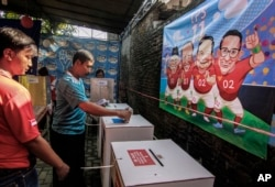 Voters cast their ballot as caricatures of presidential candidates and their running mates is are seen on the wall at a polling station in Yogyakarta, Indonesia, April 17, 2019.