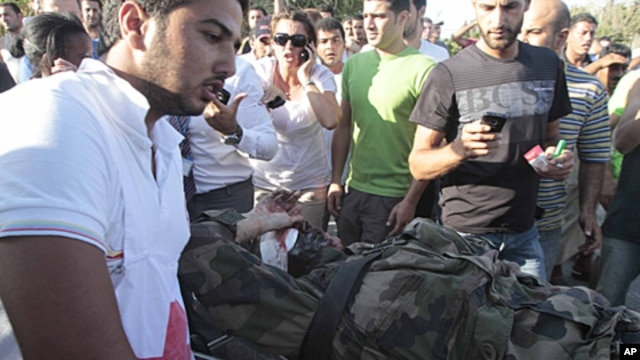 A Lebanese red cross worker, left, takes an injured French U.N. peacekeeper into an ambulance after a bomb explosion targeted a convoy of French soldiers in the southern port city of Sidon, July 26, 2011