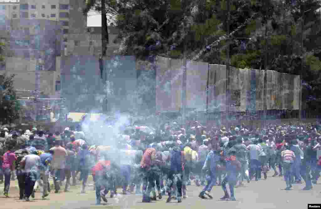 Supporters of Egypt's former President Mohamed Morsi run from tear gas during clashes with police in Cairo.