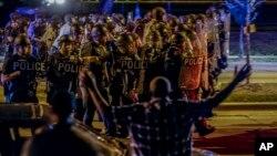 미국 밀워키에서 경찰이 흑인 청년을 총격살해한 사건에 항의하는 시위가 14일 이틀째 계속됐다. 시위진압경찰이 돌을 던지는 시위대에 맞서 전진하고 있다.