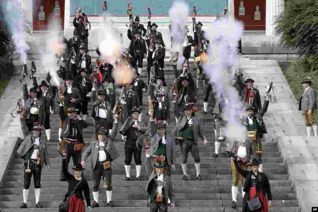 Bavarian riflemen and women in traditional costumes fire their muzzle loaders in front of the 'Bavaria' statue on the last day at the 183rd Oktoberfest beer festival in Munich, southern Germany, Oct. 3, 2016..