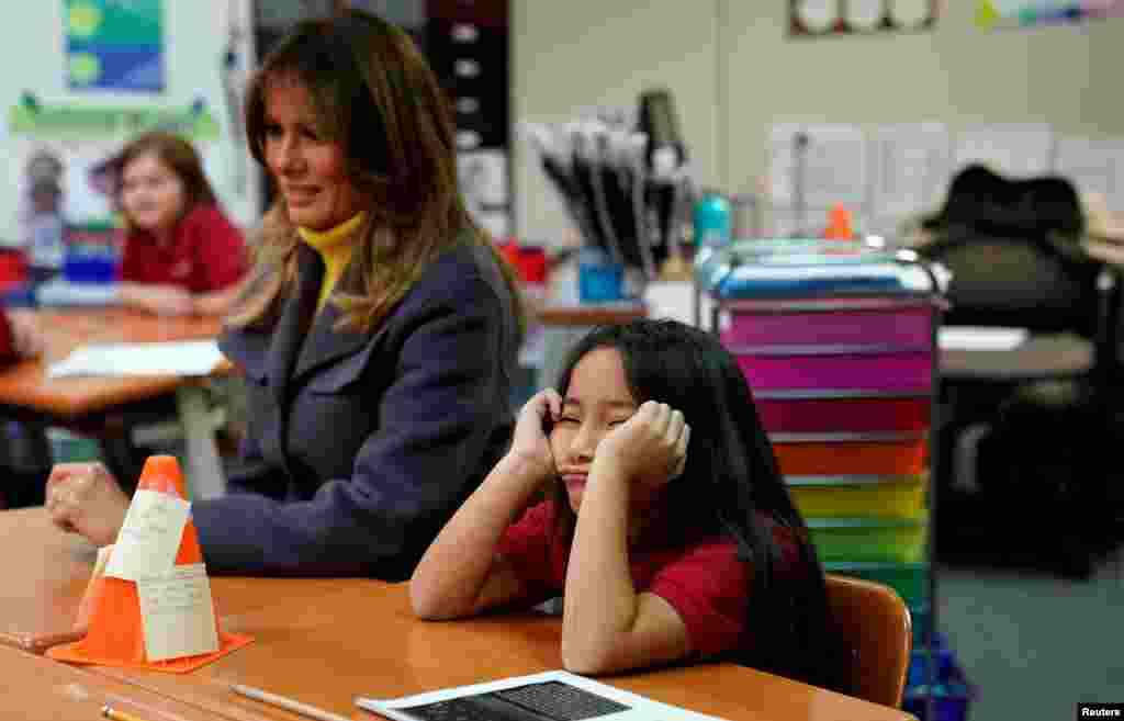 "A student sits with her head in her hands as U.S. first lady Melania Trump visits the Dove School of Discovery during a two-day, three-state tour promoting her ""Be Best"" initiative in Tulsa, Oklahoma, March 4, 2019."
