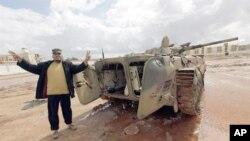 一名反卡扎菲男子在被摧毁的坦克前做胜利手势