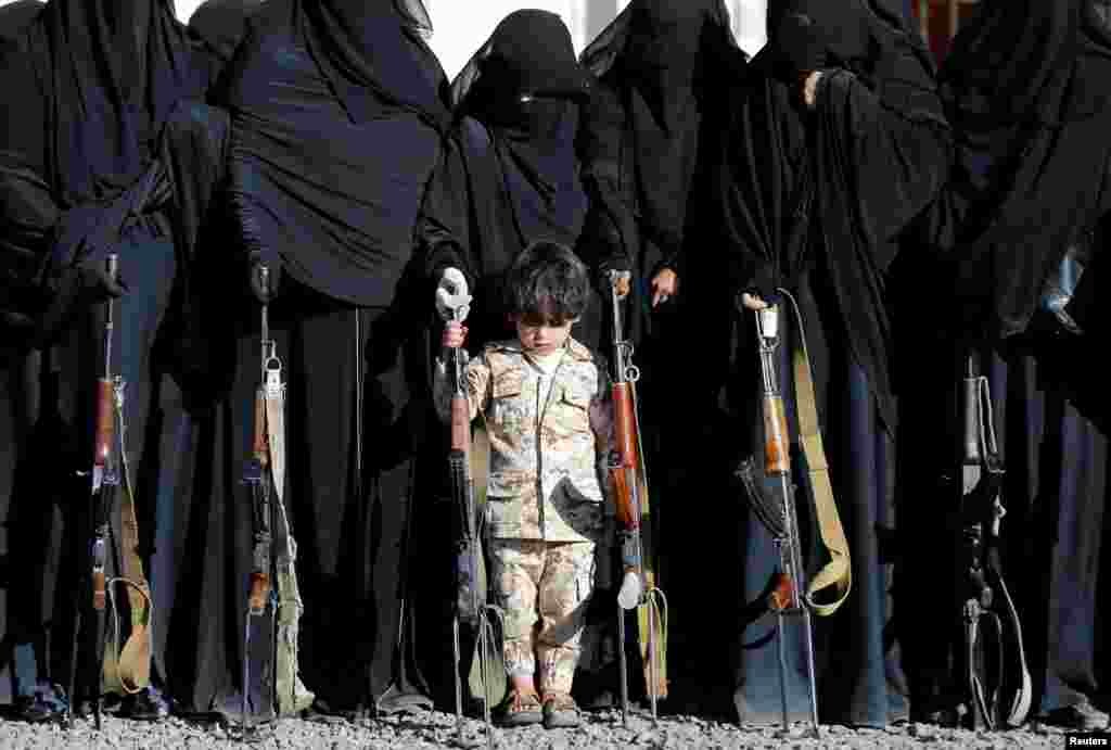 A boy stands with women loyal to the Houthi movement during a gathering held to show their support to the movement in Sanaa, Yemen.