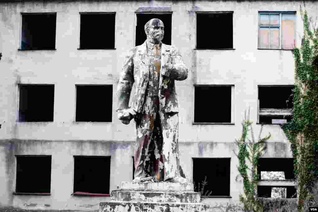 Abxaziyanın Bzipta qəsəbəsində dil məktəbinin dağıntıları qarşısında Leninin heykəli kif basır. (V. Undritz/Amerikanın Səsi)