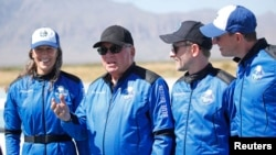 """""""Star Trek"""" actor William Shatner, 2nd left, speaks to the news media with the three other crew members after their flight in a capsule powered by Blue Origin's reusable rocket engine New Shepard, on a landing pad near Van Horn, Texas, October 13, 2021."""