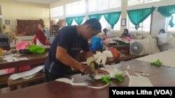 Seorang guru yang sedang memotong bahan untuk pembuatan baju alat perlindungan diri (APD) yang diproduksi di SMK Negeri 5 Palu, 31 Maret 2020. (Foto: VOA/Yoanes Litha)