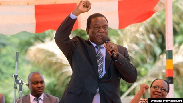 In this image taken on Wednesday Feb, 10, 2016, Zimbabwean Deputy President Emmerson Mnangagwa greets party supporters at the ZANU-PF headquarters in Harare. (AP Photo/Tsvangirayi Mukwazhi)