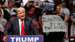 "FILE - Republican presidential candidate Donald Trump speaks at a rally as a man holds up a sign that reads ""Islamophobia is not the answer"" in Oklahoma City, Oklahoma, Feb. 26, 2016. Amnesty International has called on Trump to uphold ""the human rights of all without discrimination."""
