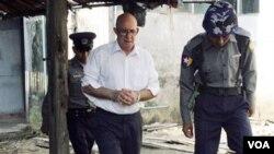Petugas keamanan Burma mengawal Ross Dunkley keluar dari pengadilan di kota Kamayut, Kamis (3/3).