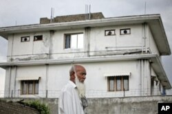 FILE - A resident walks past the compound where U.S. Navy SEAL commandos killed al-Qaida leader Osama bin Laden in Abbottabad, May 5, 2011.