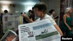 """Seorang karyawan tengah mengedarkan koran yang memuat berita tentang Edward Snowden berjudul """"Snowden akan Dinominasikan untuk Nobel"""" di sebuah jalanan bawah tanah di pusat kota Moskow (2/7). Sumber di Kementrian Luar Negeri Norwegia menyatakan bahwa Snowden telah mendaftarkan diri untuk memperoleh asilum dari negaranya."""