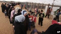 지난 1월 유엔총회 모겐스 뤼케토프트 의장이 요르단 마프라프 난민캠프를 방문한 가운데, 시리아 여성들이 유엔 지급 겨울 구호품을 받기 위해 줄을 서 있다.