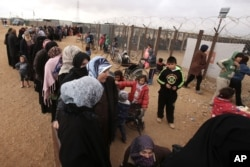 FILE - Syrian women wait in line to receive winter aid as U.N. General Assembly President Mogens Lykketoft visits Zaatari refugee camp in Mafraq, Jordan, Jan. 20, 2016.
