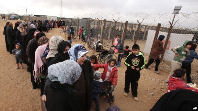 Syrian women wait in line to receive winter aid as UN General Assembly President Mogens Lykketoft visits Zaatari refugee camp in Mafraq, Jordan, Jan. 20, 2016. Jordan says the most recent census counted 1.265 million Syrians in the kingdom, or twice the number of registered Syrian refugees.
