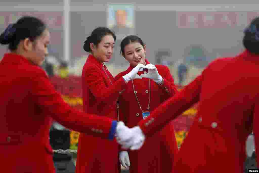 中国共产党第十九次全国代表大会在北京人民大会堂开幕之际,接待员在天安门广场拍照(2017年10月18日)。香港苹果日报说,中共十九大美女接待员成为场外亮点。
