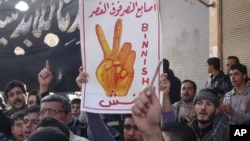 "Anti-Syrian regime protester holds up Arabic placard reading: ""the victory fingers over the [presidential] palace,"" during a demonstration, at Binnish village, in Idlib province, Syria."