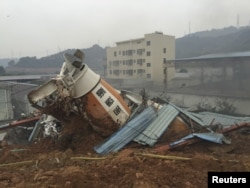 A damaged vehicle is seen among the debris at the site of a landslide at an industrial park in Shenzhen, Guangdong province, China, Dec. 20, 2015.