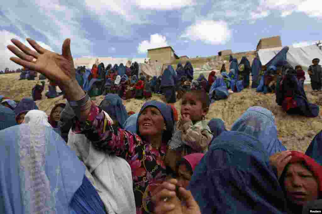 Displaced Afghans wait for aid near the site of a landslide at the Argo district in Badakhshan province.