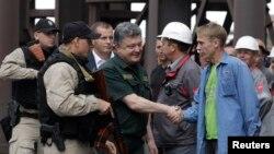 Mariupol 'da bir çelik fabrikasını ziyaret eden Cumhurbaşkanı Poroşenko işcilerle el sıkışırken