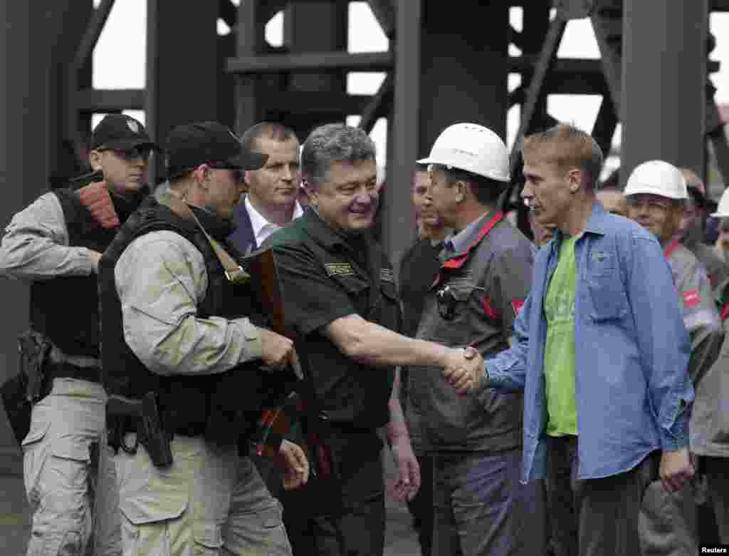 Ukrainian President Petro Poroshenko (C) shakes hands with a worker during his visit to the Ilyich Iron and Steel Works in the south-eastern port city of Mariupol September 8, 2014.
