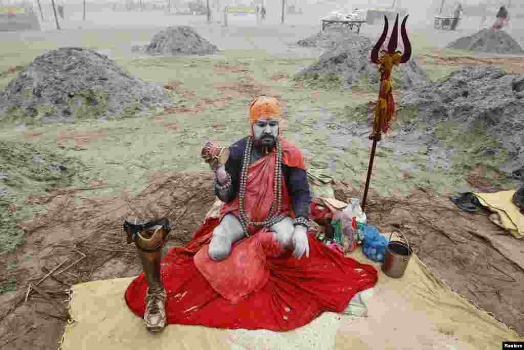 A Sadhu, or Hindu holy man, sits on the banks of river Ganges with his prosthetic leg on a cold winter morning in the northern Indian city of Allahabad.