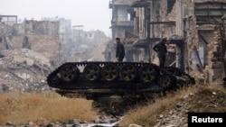 13일 시리아 알레포의 정부 관할 지역에서 정부군 병사들이 파손된 탱크 위에 서 있다.