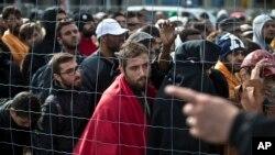 Para migran antri menunggu bus di Hegyeshalom, Hungaria yang akan membawa mereka ke Austria (6/9).
