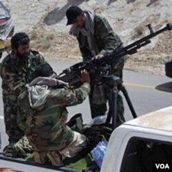 Para anggota pasukan pemberontak di luar kota Brega, Libya timur (31/3).