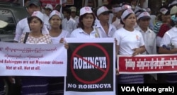 "FILE - Demonstrators hold banners outside the U.S. Embassy in Yangon, Myanmar, April 28, 2016, to protest against the embassy's use of the word ""Rohingya."""