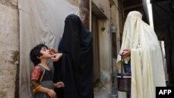 Nhân viên y tế cho trẻ em uống thuốc ngừa sốt bại liệt trong một chiến dịch chủng ngừa ở Bannu, Pakistan.
