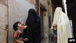 Para petugas kesehatan Pakistan memberikan vaksinasi polio pada seorang anak di Bannu.