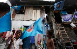 Boys hold flags of the ruling Cambodian People's Party (CPP) outside a house at a slum area in Phnom Penh July 23, 2013.