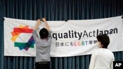 """Seorang staf memasang spanduk konferensi pers untuk meluncurkan kampanye tanda tangan internasional untuk pemberlakuan """"Hukum Persamaan LGBT"""" sebagai warisan Olimpiade Tokyo, di Tokyo, Jepang, Kamis, 15 Oktober 2020."""