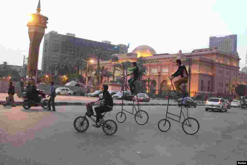 Boys ride tall bicycles in Tahrir square in central Cairo, Egypt.